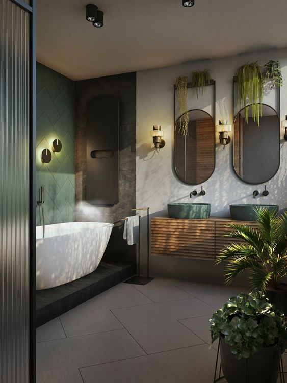 an elegant tropical bathroom with a green tile wall, green sinks, potted plants and a white tub on a platform