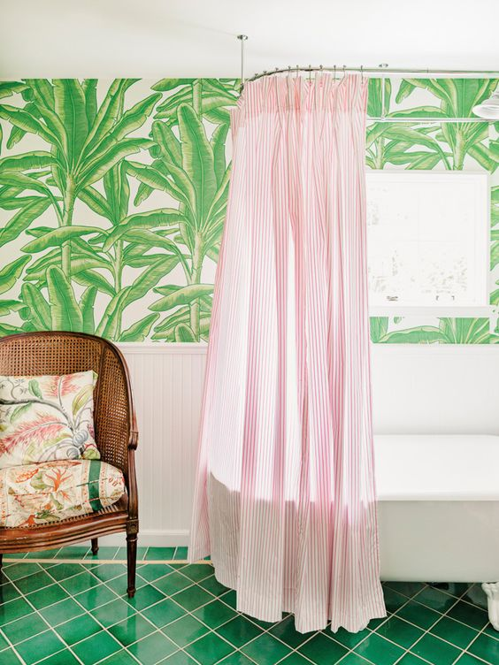 an elegant tropical bathroom with tropical leaf wallpaper, a green tile floor, a rattan chair and a pink striped curtain