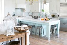an enchanting coastal kitchen with white cabinets, a light blue kitchen island and a matching backsplash, shiny pendant lamps