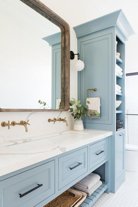 an enchanting light blue coastal bathroom with lovely vintage furniture, white marble countertops, a large wood framed mirror and touches of brass