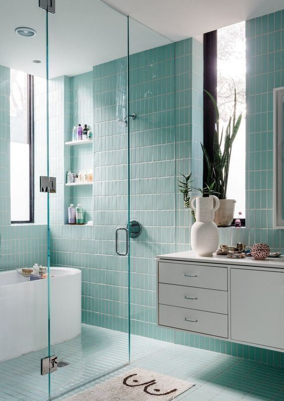 an ethereal aqua blue bathroom clad with skinny tiles, with built in shelves, a floating vanity and a fun rug