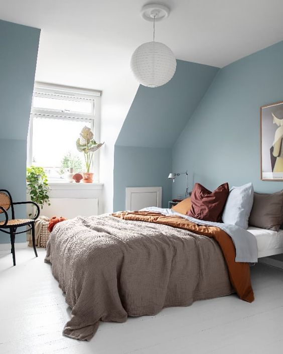 an ethereal attic bedroom with light blue walls, jewel tone bedding, a rattan chair and some potted plants