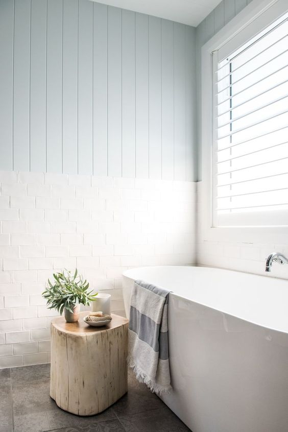 an ethereal coastal bathroom with pale blue wood and white tile walls, a free standing tub, a tree stump stool and a large window