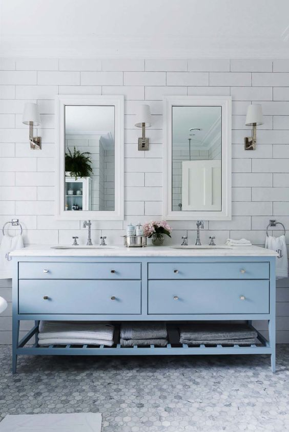 an ethereal coastal bathroom with white and marble hex tiles, a powder blue vanity, a white stone coutnertop and mirrors