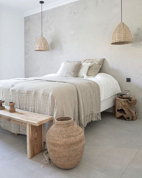 an ethereal dove grey bedroom with wicker lamps and a woven bottle, a wooden bench and nightstands and grey and white bedding