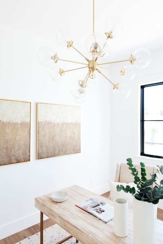 an ethereal neutral home office with a wooden desk, neutral chairs, a chic gallery wall, a gold chandelier and greenery