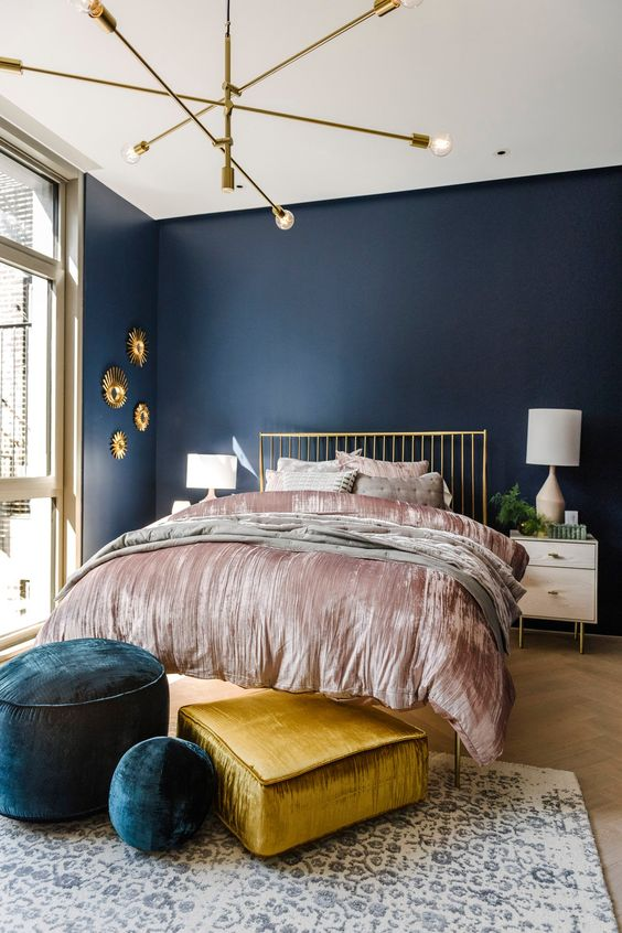 an exquisite bedroom with navy walls, a gold bed, neutral nightstands, navy and gold ottomans and a pretty gallery wall