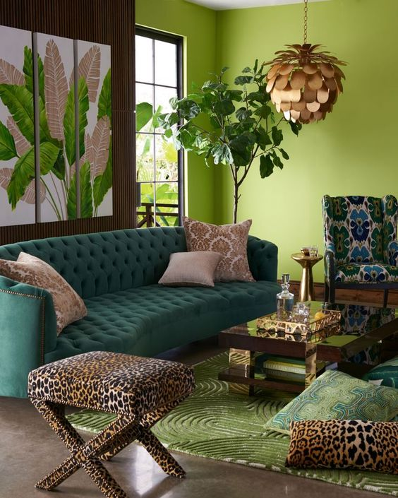 an exquisite colorful tropical living room with green walls, an emerald sofa, printed chairs and pillows