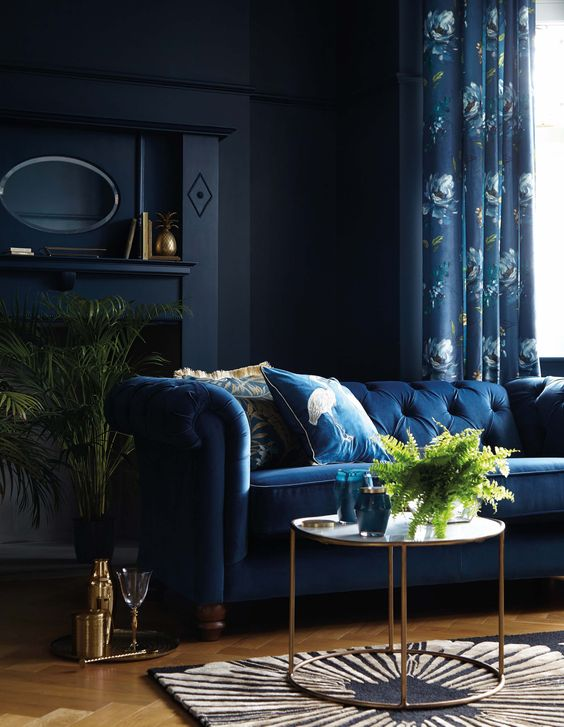 an exquisite living room with midnight blue walls, a navy sofa and floral curtains, greenery and brass touches