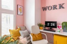 an exuberant home office with light pink walls, neutral furniture and touches of mustard – a fluffy lamp, pillows and a cabinet