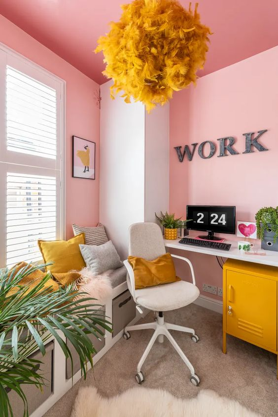 an exuberant home office with light pink walls, neutral furniture and touches of mustard - a fluffy lamp, pillows and a cabinet
