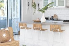 an inspiring coastal kitchen with white cabinets, a kitchen island, woven pendant lamps, wooden sotols, a wicker chair and a matching tray