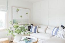 an inviting neutral coastal living room with a corner sofa, a rattan table and jute ottomans and printed pillows