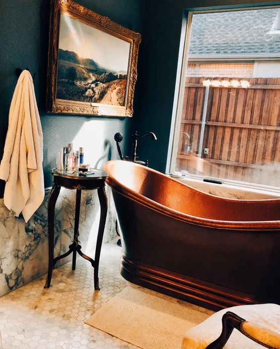 refined 19th century aesthetics with a gorgeous artwork, marble and a copper tub in front of the window