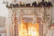 02 a brick fireplace with a white shabby chic mantel, with thin candles in candleholders inside and chic Christmas decor
