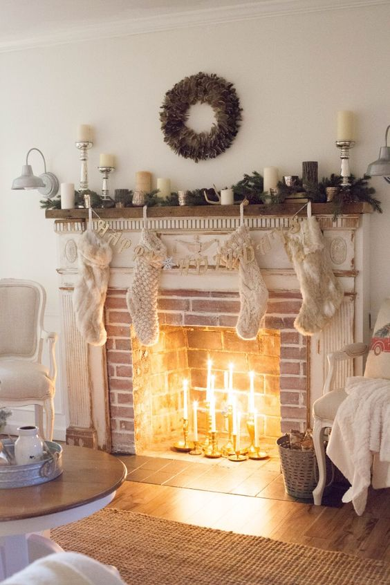 a brick fireplace with a white shabby chic mantel, with thin candles in candleholders inside and chic Christmas decor
