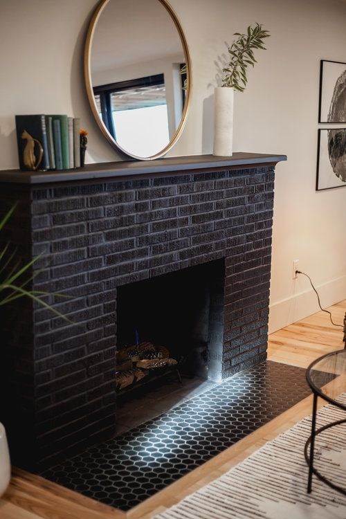 an elegant black brick fireplace with matching black hex tiles in front of it is a cool decor feature for any space