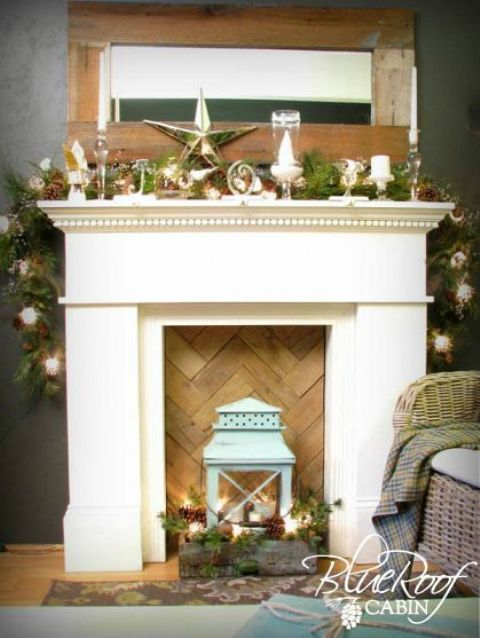 a faux fireplace with a chevron wooden screen, a crate with pinecones, candles, fir brnahces and a blue lantern