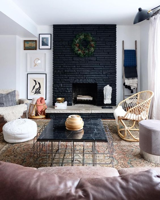 an eclectic living room with a black brick fireplace, stone and a greenery wreath and a black marble table that echoes with it
