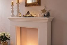 04 a faux fireplace with white pillar candles, neutral ornaments and stars for creating a Christmas ambience