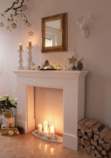 a faux fireplace with white pillar candles, neutral ornaments and stars for creating a Christmas ambience