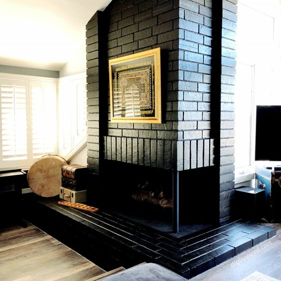 a vintage-inspired black brick fireplace with a stack of suitcases next to it, an artwork for a unique touch in the room