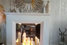 05 a faux white fireplace with a mirror screen and pillar candles, a sunburst mirror, vases on the mantel for decor