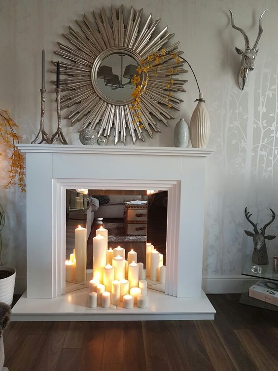 a faux white fireplace with a mirror screen and pillar candles, a sunburst mirror, vases on the mantel for decor