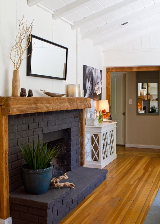 a stylish black brick fireplace with a rough wood mantel and frame, with some decor is a bold decor feature