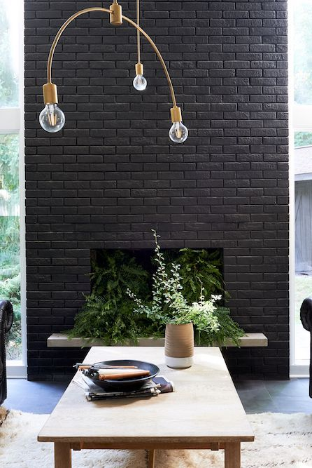 a black brick fireplace filled with potted greenery is a bold decor feature in this neutral living room and it stands out a lot