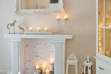 06 a faux white fireplace with candles placed on tree stumps, with candle lanterns and candles on the mantel