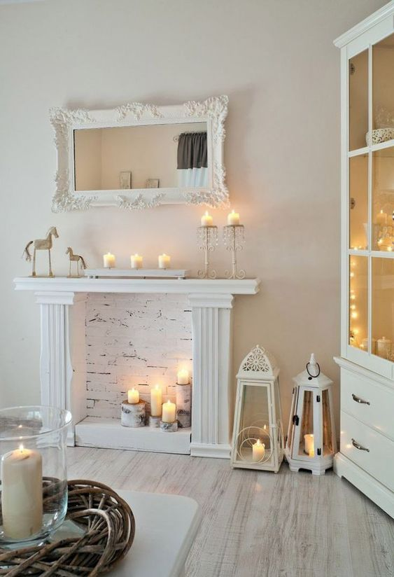 a faux white fireplace with candles placed on tree stumps, with candle lanterns and candles on the mantel