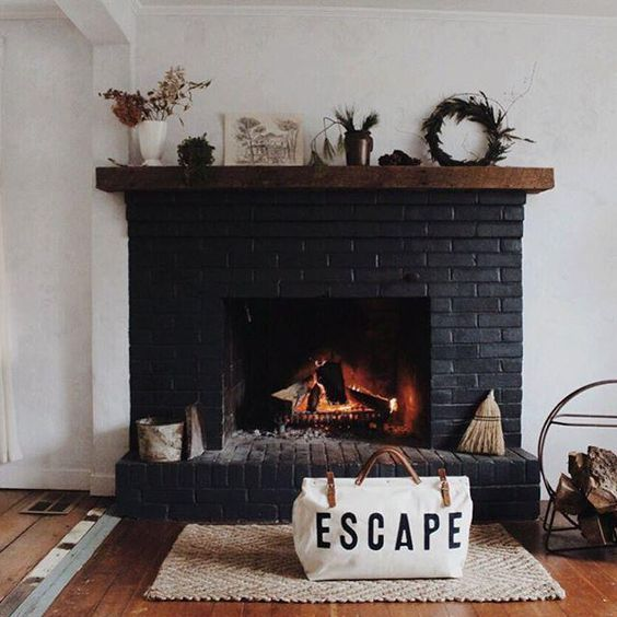 a black brick fireplace with a wooden mantel with various plants and some accessories plus a firewood stand next to it