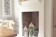 07 a large non-working fireplace with bricks inside, candle lanterns, flwoers and whitewashed baskets is chic