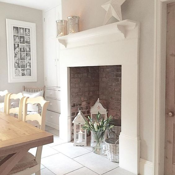 a large non working fireplace with bricks inside, candle lanterns, flwoers and whitewashed baskets is chic