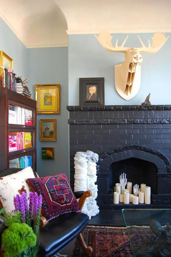 a black brick fireplace with pillar candles and hands, with a faux deer head over it is very cool and bold