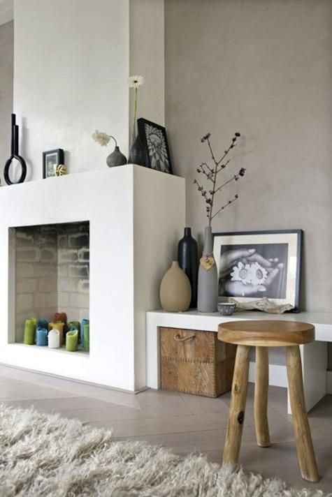 a modern non working fireplace with colorful candles inside looks bold and fun and sticks to the style of the room