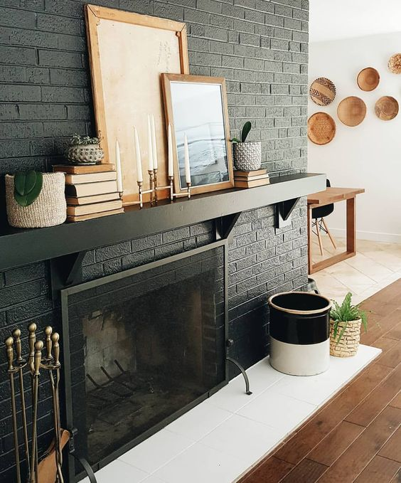 a black brick fireplace with white tiles in front of it, a black mantel with books and artworks for stylish monochromatic decor