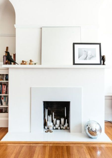 a neutral minimal faux fireplace with lots of various candles inside and very laconic and minimal decor on the mantel