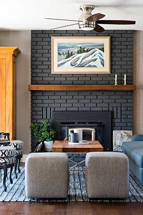 a black faux brick fireplace with a wooden mantel and some artworks around for a stylish and elegant look