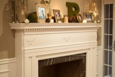 10 a non-working fireplace of brick, marble, with a refined white mantel and candles in glasses inside plus chic and catchy decor on the mantel