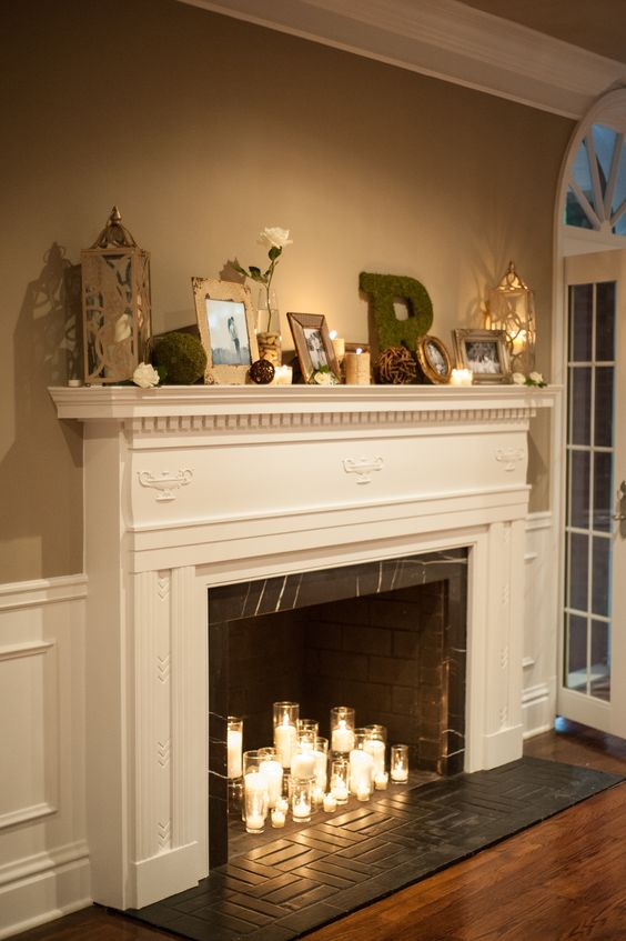 a non working fireplace of brick, marble, with a refined white mantel and candles in glasses inside plus chic and catchy decor on the mantel