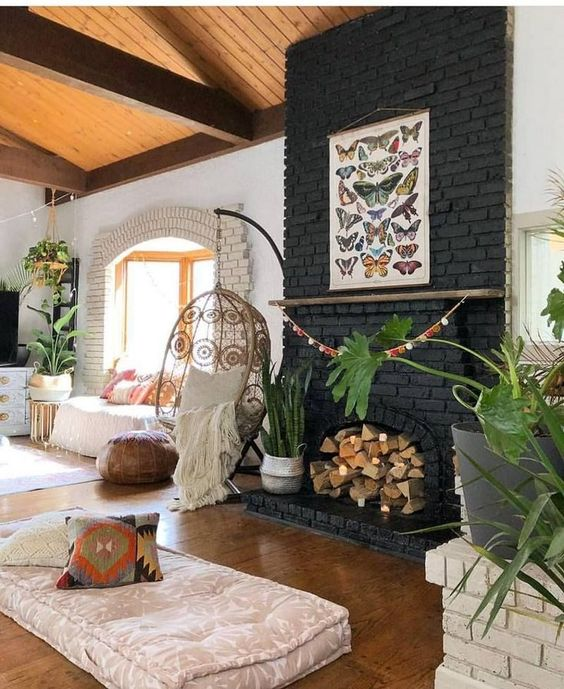 a boho living room with a black brick fireplace filled with firewood and plants in baskets plus a butterfly poster on it