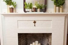 11 a non-working fireplace of brick, with a metal stand for firewood and pillar candles on it