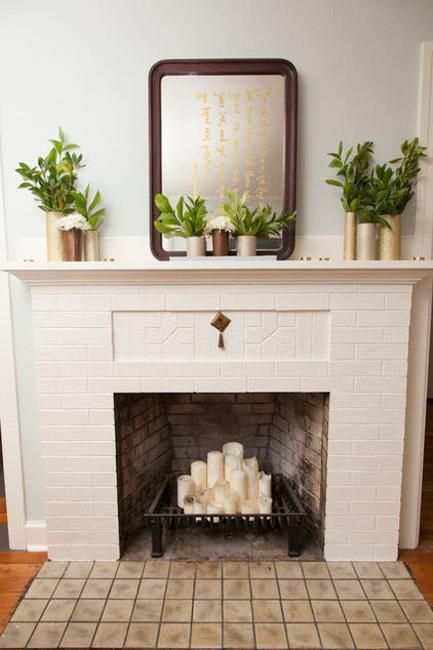 a non working fireplace of brick, with a metal stand for firewood and pillar candles on it