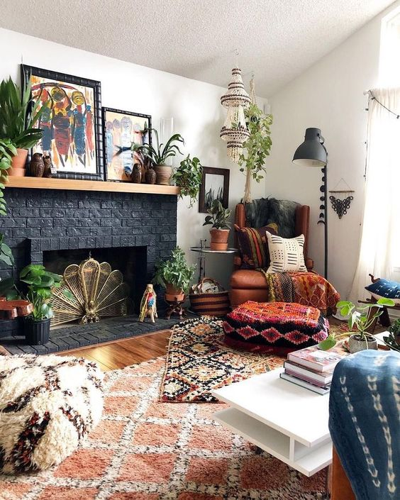a boho living room with a black brick fireplace and a wooden mantel, with lots of potted plants and bold boho artworks