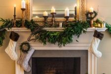 12 a non-working fireplace styled for winter, with dark bricks and candle lanterns inside plus candles on the mantel