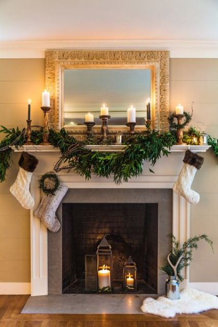 a non-working fireplace styled for winter, with dark bricks and candle lanterns inside plus candles on the mantel
