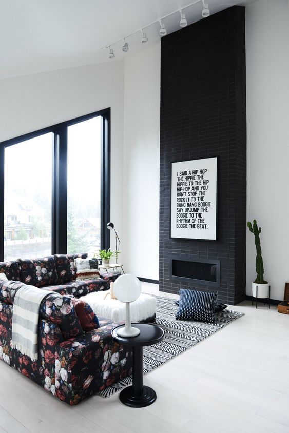 a laconic black brick fireplace with a graphic artwork to finish off a monochromatic look and a floral sofa to spruce up the space