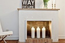 13 a non-working fireplace with bricks inside and out and pillar candles for styling it right